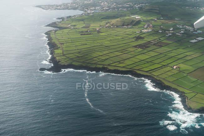 Vue aérienne de champs verts et bleu océan ondulé. — Photo de stock
