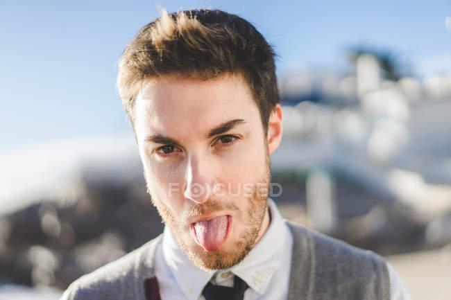 Jeune homme barbu dans des vêtements élégants montrant la langue à la caméra — Photo de stock