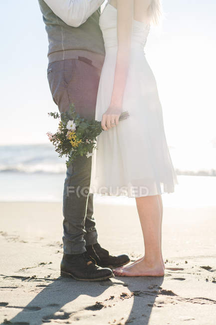 Crop bride with bouquet embraced by groom at beach — Stock Photo
