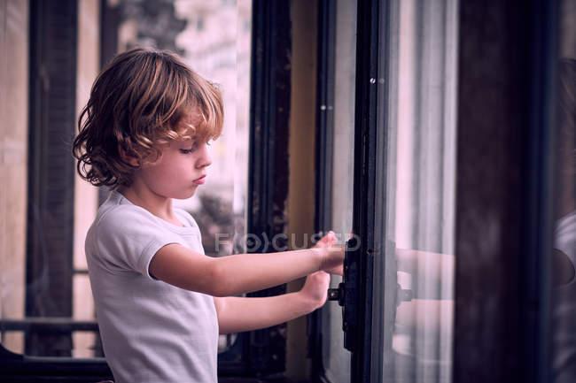 Seitenansicht eines kleinen Jungen, der am Fenster steht und nachdenklich wegschaut — Stockfoto