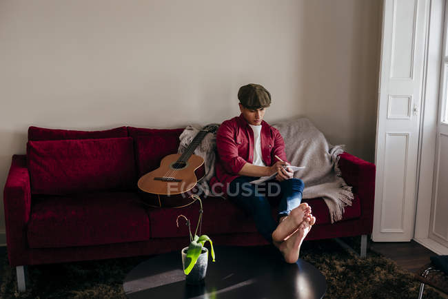 Jeune homme au chapeau assis sur le canapé de guitare et de prendre des notes — Photo de stock