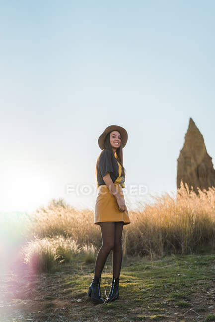 Cheerful brunette woman in hat looking over shoulder at camera at countryside — Stock Photo