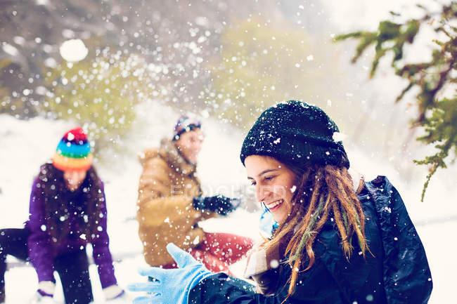 Amigos felizes jogando bolas de neve no bosque nevado — Fotografia de Stock