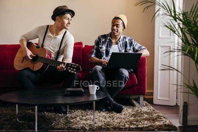 Os jovens elegantes, descansando no sofá, com guitarra e laptop — Fotografia de Stock