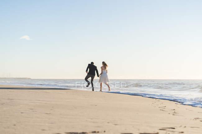 Vista traseira da noiva e do noivo, passear na praia — Fotografia de Stock