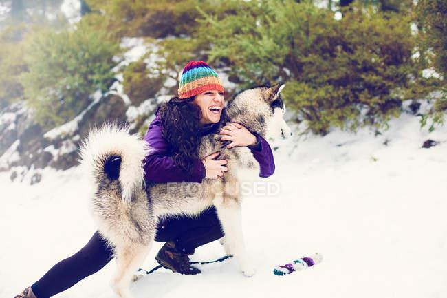 Rir cão abraçando mulher em Neves — Fotografia de Stock