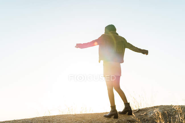 Rear view of young woman posing on hill against sky — Stock Photo