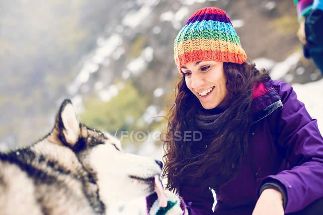 Mulher sorridente, brincando com cachorro na neve — Fotografia de Stock