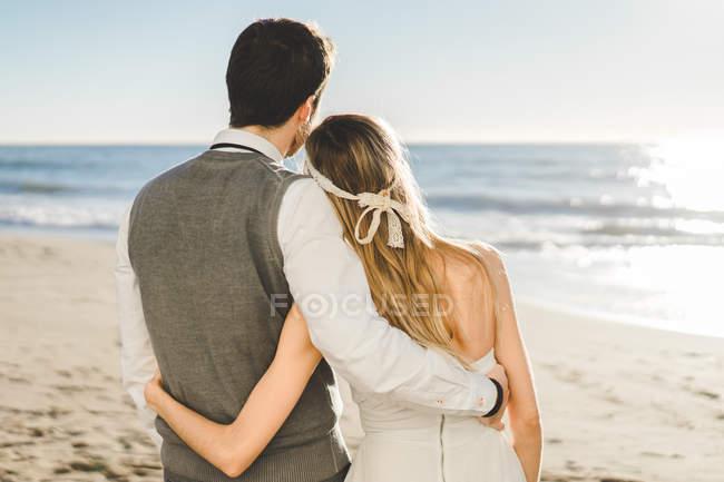Novia pareja abrazándose en la playa idílica - foto de stock