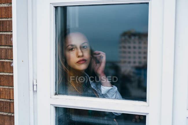 Jeune femme touchant l'oreille et regardant la caméra par la fenêtre à la maison . — Photo de stock