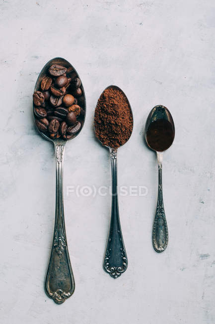 Coffee beans, ground coffee and black coffee in retro spoons — Stock Photo