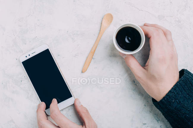 Crop male hands holding black coffee in disposable cup and smartphone — Stock Photo