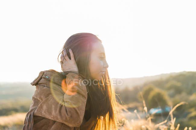 Чуттєва жінка, регулюючи волосся в природі — стокове фото