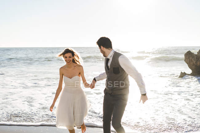 Outstanding Happy Bride And Groom Holding Hands And Running On Seaside Download Free Architecture Designs Scobabritishbridgeorg