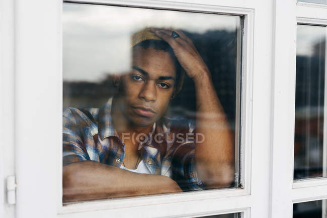 Thoughtful young man standing behind window and looking at camera. — Stock Photo