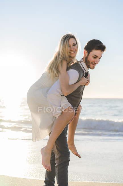 Noivo de jovem garota alegre carregando nas costas na praia — Fotografia de Stock