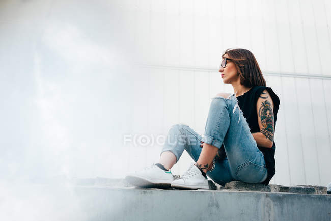 Вид сбоку на татуированную женщину, сидящую на тротуаре — стоковое фото
