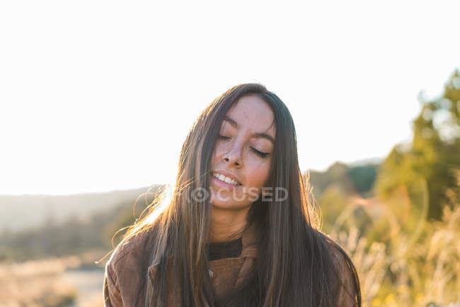 Cheerful woman posing in nature with eyes closed — Stock Photo