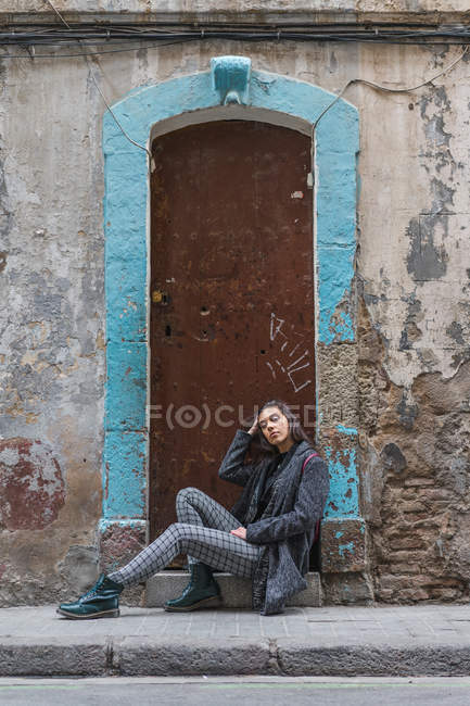 Young woman leaning on grungy doorsteps at street — Stock Photo