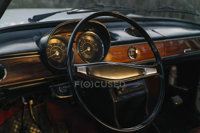Dashboard with wooden panels and steering wheel of retro car. — Stock Photo