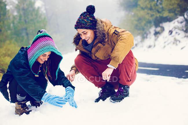 Casal feliz fazendo boneco de neve na estrada na floresta — Fotografia de Stock