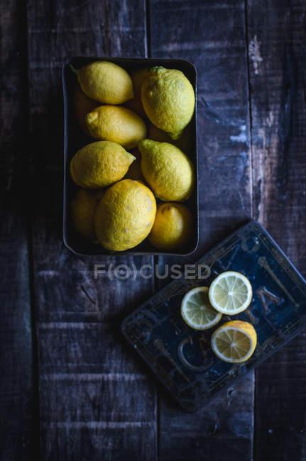 Сверху свежий весь и нарезанные лимоны на деревянный стол. — стоковое фото