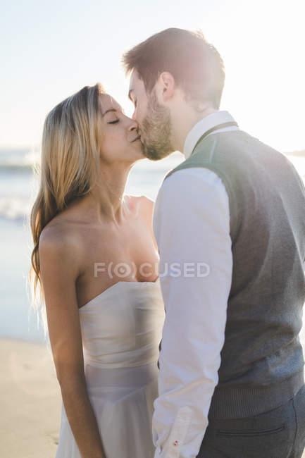 Молодая нежная пара целуется на солнце — стоковое фото