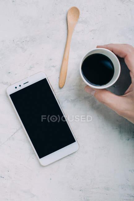 Ernte männliche Hand, die schwarzen Kaffee in Einweg-Becher per smartphone — Stockfoto