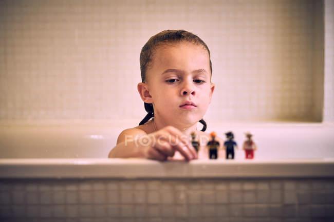 Petit garçon mignon jouant avec des jouets sur le bord du bain — Photo de stock