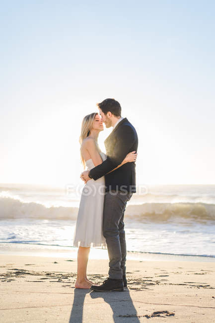 Sensual bridal couple kissing in sunlight — Stock Photo