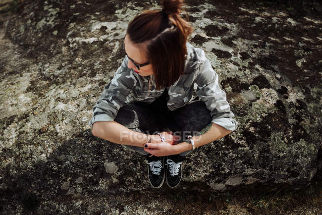 Woman in glasses sitting at stones ans looking aside — Stock Photo