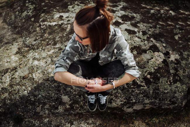 Femme à lunettes assis à pierres ans regardant de côté — Photo de stock