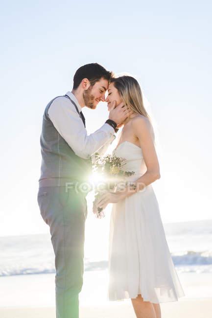 Жених обнимает невесту с букетом на солнечном пляже — стоковое фото