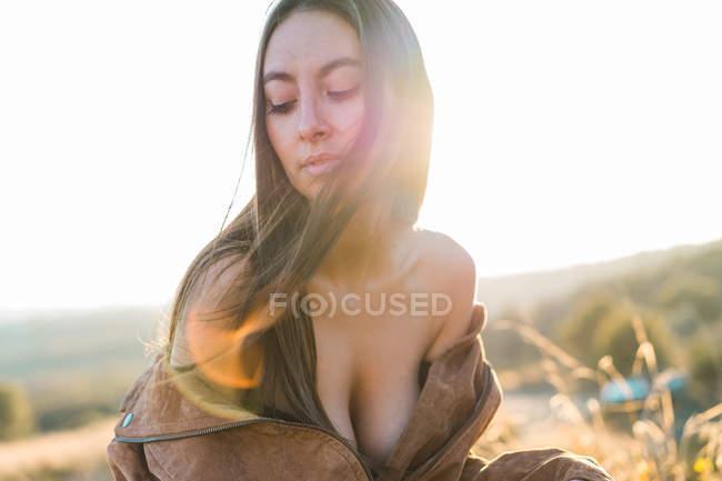 Sensuelle jeune femme se déshabiller et assis dans la nature dans la journée ensoleillée . — Photo de stock