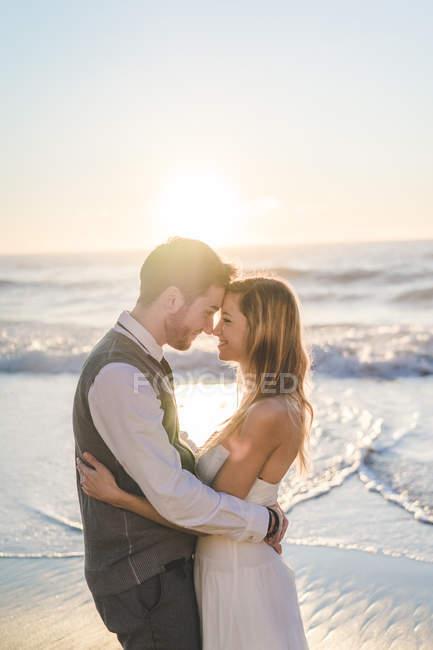 Нежная супружеская пара позирует лицом к лицу на побережье океана — стоковое фото