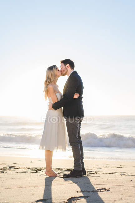 Young bridal couple kissing on beach in sunlight — Stock Photo