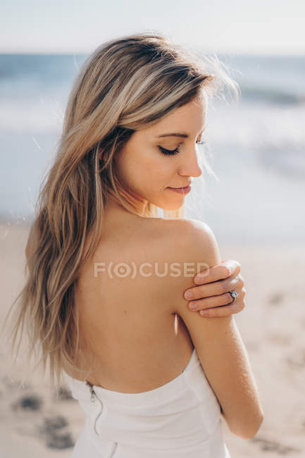 Young woman with long hair posing sensually in dress in sunlight. — Stock Photo