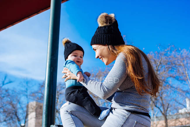 Side view of young mother playing with cute toddler at park — Stock Photo