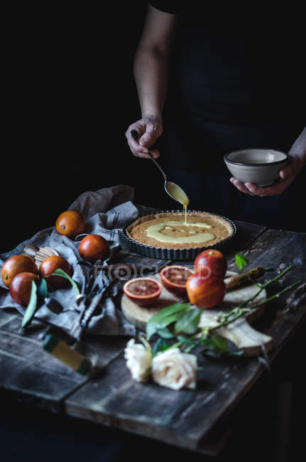 Erntehelferin legt Pudding auf Torte am Tisch — Stockfoto