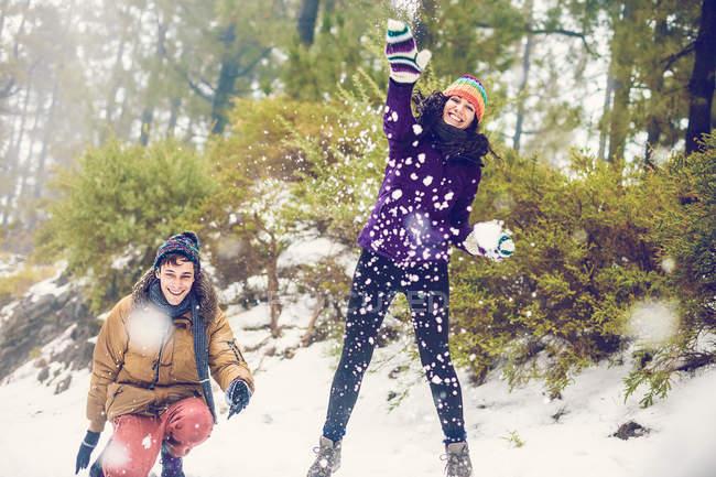 Amigos felizes jogando bolas de neve na floresta — Fotografia de Stock