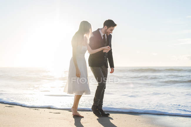 Romantic bride and groom holding hands and walking on beach — Stock Photo