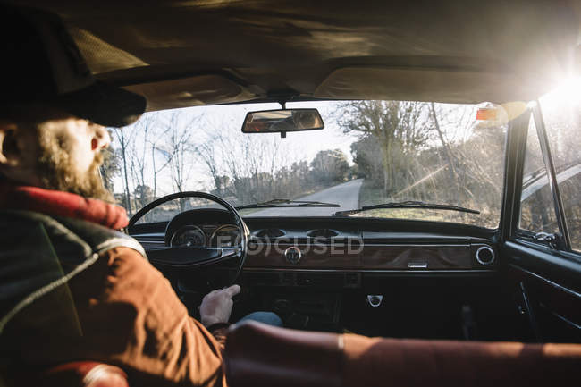 Handsome adult man in hat driving white car in nature. — Stock Photo
