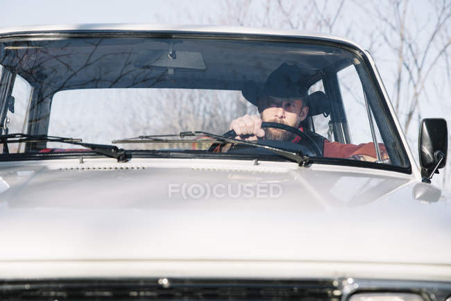 Man in hat driving white car in nature. — Stock Photo