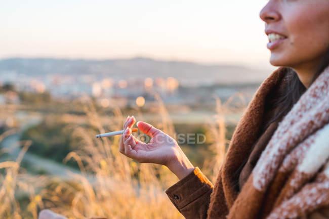 Imagem cortada de mulher fumando cigarro na natureza — Fotografia de Stock