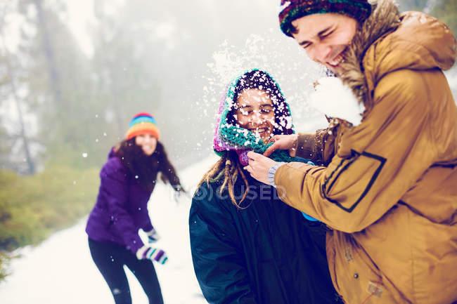 Grupo de amigos jogando bolas de neve na floresta a rir — Fotografia de Stock