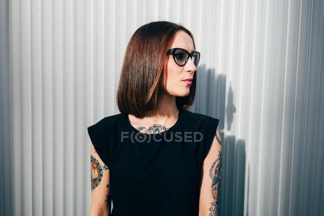 Elegante donna bruna in piedi al muro di metallo — Foto stock
