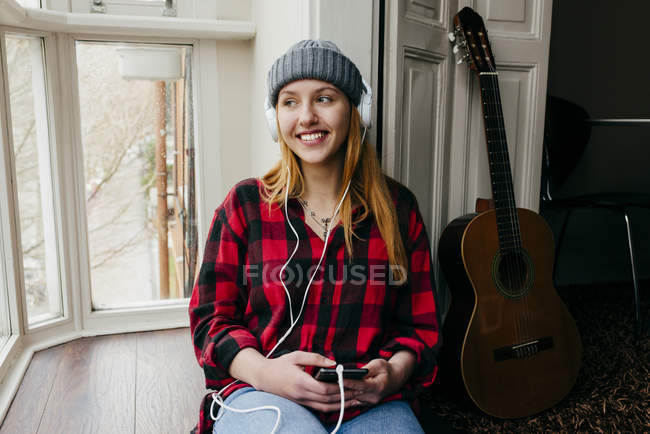 Cheerful blonde woman listening music with smartphone at home — Stock Photo