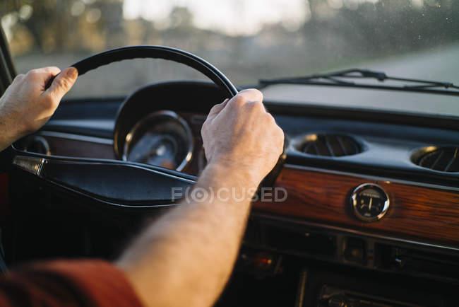 Обтинання чоловічої руки на рульове колесо ретро-автомобіль. — стокове фото