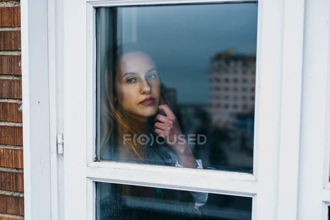 Serena donna bionda posa dietro la finestra — Foto stock