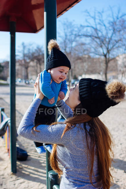 Mother holding cute toddler in midair at playground — Stock Photo